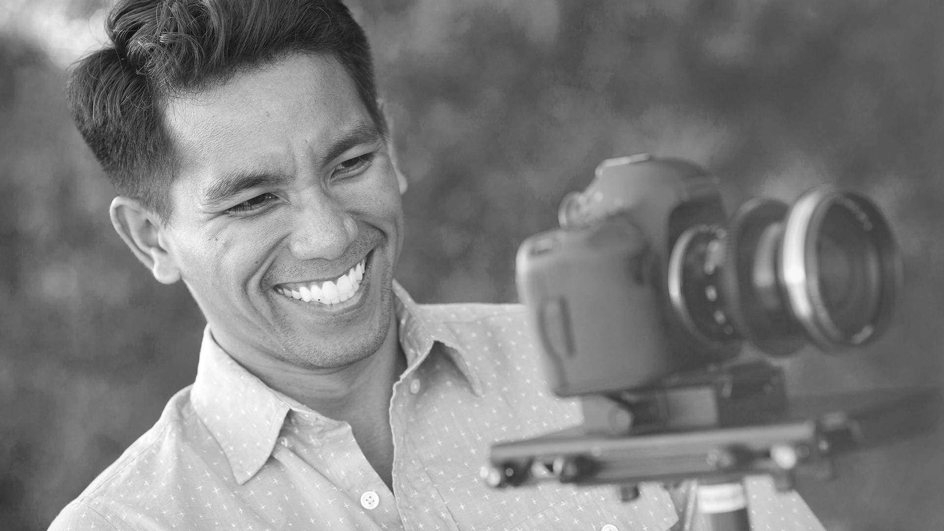 Guy smiling while looking into camera display